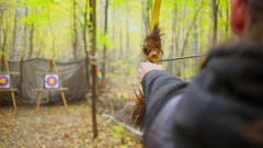 Man shoots arrow from bow to aim in forest at autumn day Stock Footage