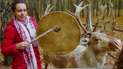 Woman beats tambourine and girl pats stuffed deer at autumn day Stock Footage