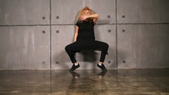 Blonde girl in black dress dances on floor near wall Stock Footage