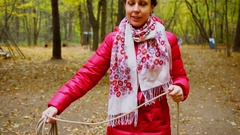 Woman in colorful scarf throws rope at autumn day in forest Stock Footage