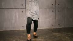 Legs of woman in gray dress which dances near wall Stock Footage