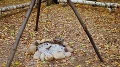 Chain sways on tripod above fire place at autumn day in forest Stock Footage