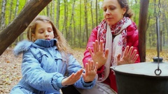 Woman and girl warm hands near kettle and smolder log Stock Footage