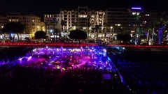 Night club on beach near Croisette boulevard with crowd of people and traffic Stock Footage