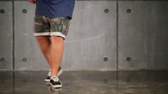 Legs of man which dance in shorts on floor near wall Stock Footage