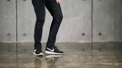 Legs of boy and girl which dance on floor near wall Stock Footage