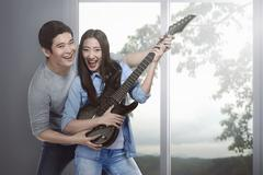 Attractive asian couple in love playing guitar Stock Photos
