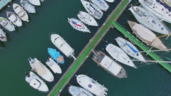 Several boats on moorage near pier with green carpet. Aerial view Stock Footage