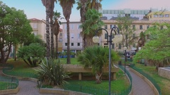 Palms on street with traffic next to Ariston theater at summer day Stock Footage