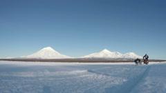 Dog sled racing on background of Kamchatka volcanoes Stock Footage