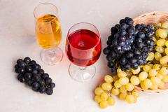 Wine and grapes. White and red wine in glasses on light marble background. Stock Photos