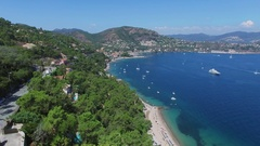 Traffic on mountain road and vessels sail by sea bay near coastal town Stock Footage
