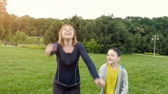 Mother and her child jumping in park zone.Slow motion. Stock Footage
