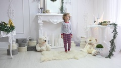 Girl in pajamas jumping on the bed. The concept of Christmas. Photoshoot with Stock Footage