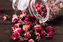 Rose petals and dried flowers in jar on old wooden table. healthy concept Stock Photos
