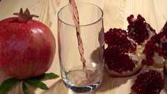Fresh pomegranate juice is pouring into a glass on a wooden table. Stock Footage