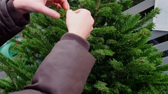 Hands girls decorate artificial Christmas tree outdoor Stock Footage