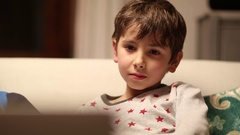 Child watching cartoon before going to bed Young boy hypnotized  Stock Footage