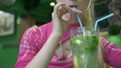 Close Up of a Young Girl is Drinking Mojito with Mint in Restaurant Arkistovideo