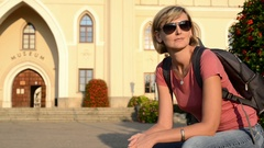 Woman tourist sitting outdoors, with castle at background Stock Footage
