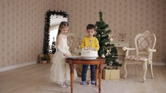 Little sister and brother decorate Christmas cake. beautiful children in a Stock Footage