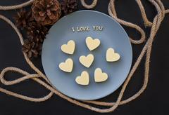 Candy white chocolate in a heart, I love writing on a blue plate with cones Stock Photos