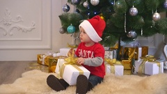 Cute boy in a santa hat and bow tie tying a ribbon on a gift Stock Footage