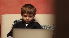 Child in front of screen watching cartoon content Young boys hypnotized by scree Stock Footage