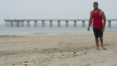 A young man doing speed and agility training on the beach, slow motion. Stock Footage