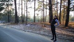 Athletic middle aged woman stretching in the green leaved woods on a dirt road Stock Footage