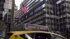 Taxi cab what's next ad and American flag waving office building Manhattan NYC Stock Footage