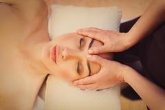 Professional masseuse massaging female face Stock Photos