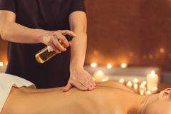 Skillful masseuse serving client at spa Stock Photos