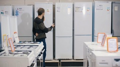 Man choosing new refrigerator in domestic appliances store Stock Footage