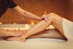 Professional masseuse massaging foot of girl Stock Photos