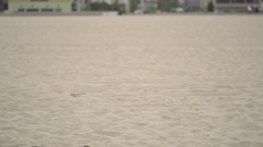 A man doing speed and agility training with parachutes on the beach , super slow Stock Footage