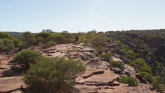 Girl hiking on red rock above dry Murchison river Stock Footage