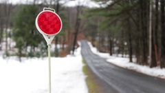 Red Road Reflector on a snowy woodland road Stock Footage