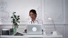 Young female doctor looking for x-ray photo and making notes Stock Footage