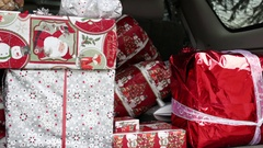 Hand putting presents in trunk of SUV Stock Footage