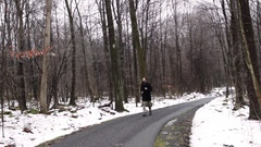 Bearded man runs down snowy trail in wintry forest Stock Footage