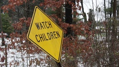 Leaning Watch Children sign in snowy forested road Stock Footage