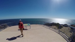 Man walking over steep red sea cliffs of Kalbarri NP in Australia Stock Footage