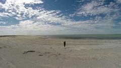 Person amid Millions of tiny white shells on Australia shell beach Stock Footage