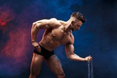 Handsome power athletic man bodybuilder doing exercises with chain. Fitness Stock Photos