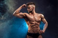 Handsome power athletic man bodybuilder. Wet Fitness muscular body on dark smoke Stock Photos