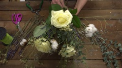 Florist at work arranging flowers into a bouquet. Stock Footage