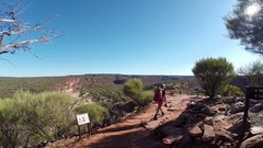 Man walking on red rocks over almost dry Murchison River bed in Kalbarri NP Stock Footage