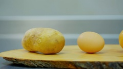 Potatoes, onion, egg and flour lying on a wooden stand Stock Footage