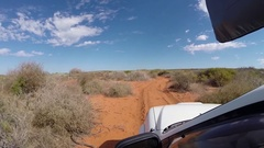4x4 vehicle driving on red earth sand road in Australia Stock Footage